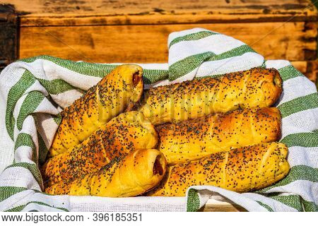Sausages Baked In Dough Sprinkled With Salt And Poppy Seeds In A Rustic Basket. Sausages Rolls, Deli