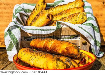Sausages Baked In Dough Sprinkled With Salt And Poppy Seeds In A Rustic Composition. Sausages Rolls,