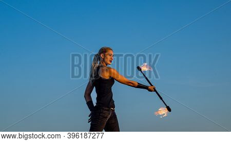 Flirting With Danger. Sexy Fire Performer Blue Sky. Sensual Woman Manipulate Flaming Rod. Fire Perfo