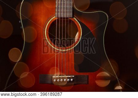 Acoustic Guitar. Part Of The Case And Strings On A Black Background.