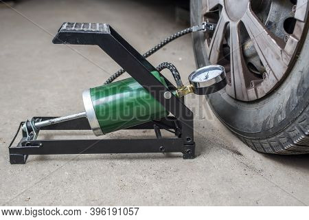 Foot Pump Near The Car With Flat Tire On The Road. Foot Pump For Pumping A Car Tire. Car Repairs. Ma
