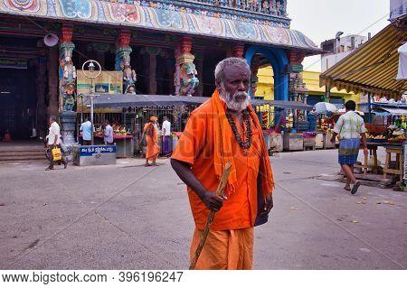 Madurai, India - November 02, 2018: An Old Man In Orange Hindu Traditional Wear Walking With A Stick
