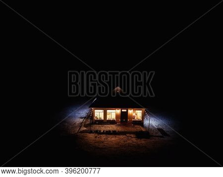 Lonely Illuminated House Among Darkness, Aerial View. Loneliness And Solitude Concept
