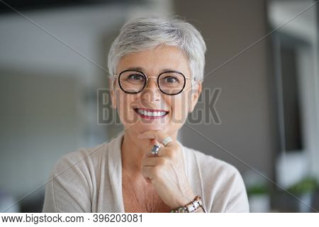 Portrait of a attractive smiling 55-year-old woman with white hair