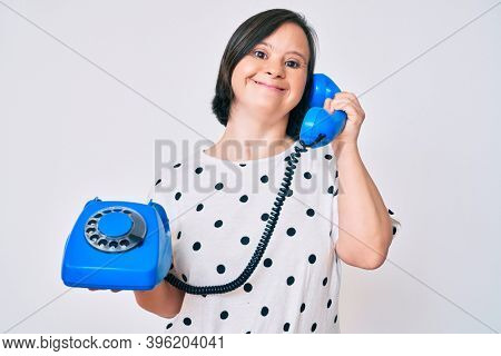Brunette woman with down syndrome holding vintage telephone smiling with a happy and cool smile on face. showing teeth.