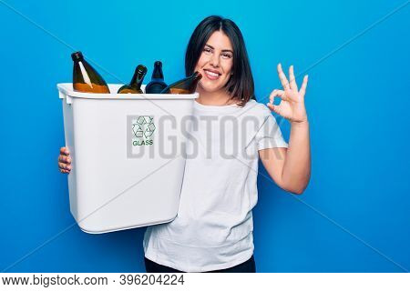 Young beautiful woman recycling glass bottles on wastebasket to care environment doing ok sign with fingers, smiling friendly gesturing excellent symbol