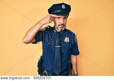 Middle age hispanic man wearing police uniform pointing unhappy to pimple on forehead, ugly infection of blackhead. acne and skin problem