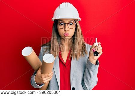 Beautiful brunette woman wearing safety helmet holding blueprints puffing cheeks with funny face. mouth inflated with air, catching air.