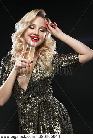 New Year, Birthday, holiday concept: Young blonde woman in evening dress holding glass of champagne over dark background