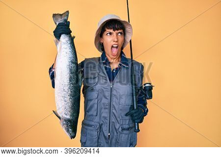 Beautiful brunettte fisher woman holding fishing rod and raw salmon angry and mad screaming frustrated and furious, shouting with anger. rage and aggressive concept.