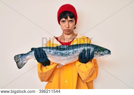 Beautiful brunettte fisher woman wearing raincoat holding fresh salmon depressed and worry for distress, crying angry and afraid. sad expression.