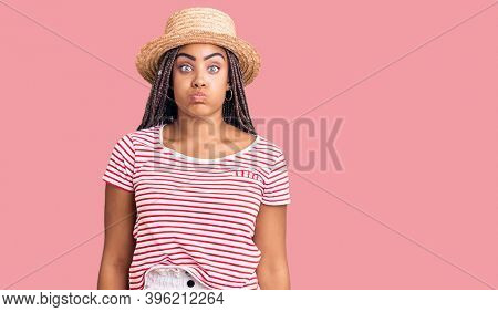 Young african american woman with braids wearing summer hat puffing cheeks with funny face. mouth inflated with air, crazy expression.