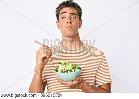Young handsome man eating salad puffing cheeks with funny face. mouth inflated with air, catching air.