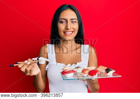 Young brunette woman eating butterfish sushi using chopsticks winking looking at the camera with sexy expression, cheerful and happy face.