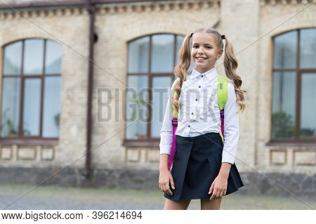 Happy Kid With Long Hair Tails Back To School Wearing Fashion Uniform In Schoolyard Outdoors, Septem