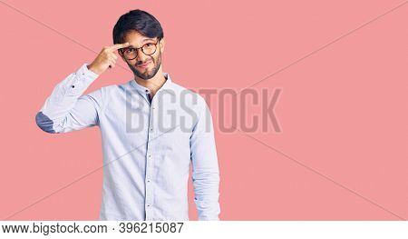 Handsome hispanic man wearing business shirt and glasses pointing unhappy to pimple on forehead, ugly infection of blackhead. acne and skin problem