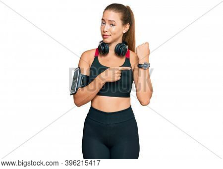 Beautiful blonde woman wearing gym clothes and using headphones in hurry pointing to watch time, impatience, looking at the camera with relaxed expression