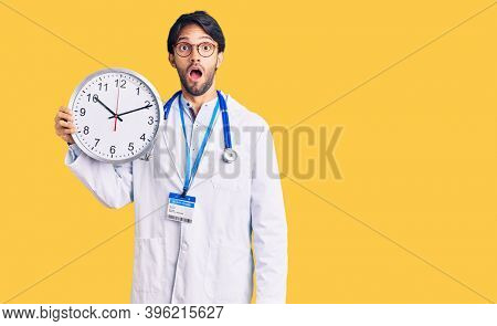 Handsome hispanic man wearing doctor uniform holding clock scared and amazed with open mouth for surprise, disbelief face