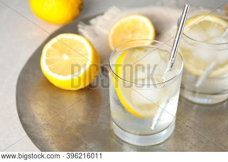 Soda Water With Lemon Slices And Ice Cubes On Silver Tray