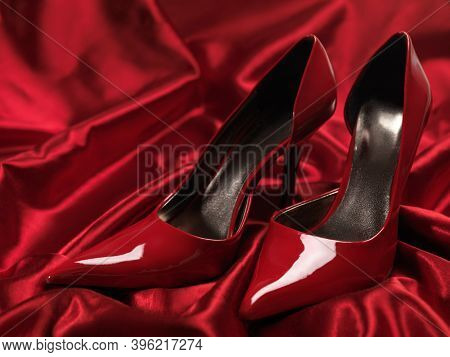 Red sexy high heel shoes on silky satin fabric