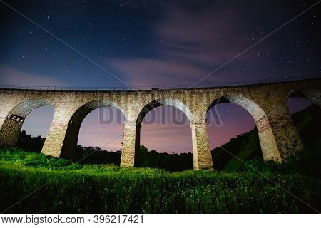 Fantastic starry sky over the old viaduct. Location village of Plebanivka, Ukraine, Europe. Popular european tourist place. Long exposure shot, astrophotography. Discover the beauty of earth.