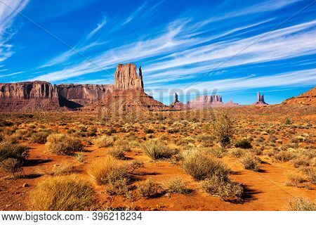 Monument Valley is geological formation. The USA. Huge masses of red sandstone - outliers on the Navajo Indian Reservation. Dry grass bushes. The concept of active and photo tourism
