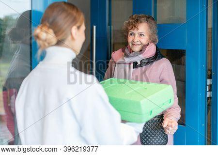 Volunteer delivering a hot meal to door of senior citizen