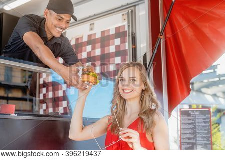Beautiful woman getting a burger as takeout food from cook in food truck which makes her visibly happy