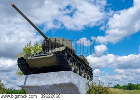 Old Soviet Tank T-34 From The Second World War On A Pedestal. Against The Backdrop Of A Beautiful Cl