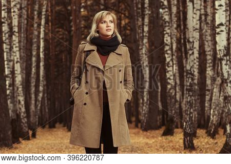 Happy young blonde fashion woman with handbag walking in autumn park Stylish female model in classic beige coat and black scarf