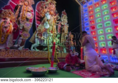 Blurred Image Of Hindu Bengali Purohit Kneeling Down In Respect And Parying To Goddess Durga Inside