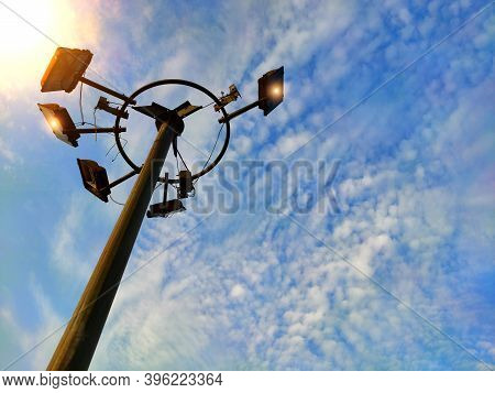 High Light Pole Or Electric Flood Lamp Against Blue Sky In Urban City Background Used For Lightening