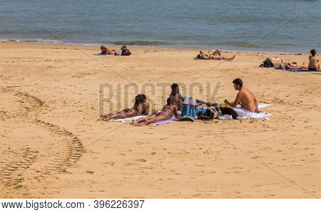 CASCAIS, PORTUGAL - SEPTEMBER 19, 2020: People sunbathing on the Praia da Rainha beach in Cascais, Portugal. Cascais is famous and popular summer vacation spot for Portuguese and foreign tourists