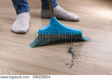 The Man Sweeps The Debris Into A Blue Scoop With A Brush.
