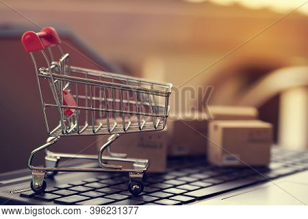 Online Marketing And Payment Concept: Shopping Cart With Smartphone On Laptop Computer And Icon Onli