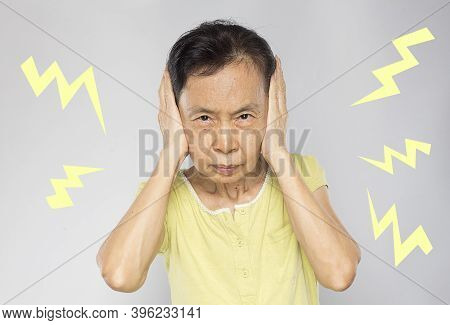 Old Asian Woman Feel  Annoyed And Covered Her Ears With Her Hands And Felt Noisy With The Surroundin