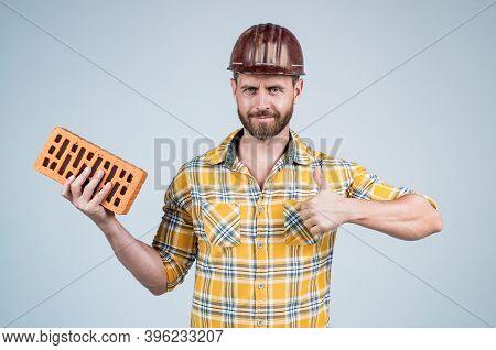 Builder Enjoy Success. Man Architect With Brick. Guy Wear Worker Uniform. Handsome Builder In Helmet