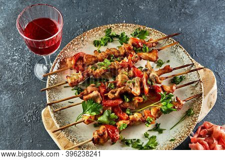 Japanese Style Yakitori Shashlik On A Wooden Board With A Glass Of Red Wine And Ginger. Flat Lay