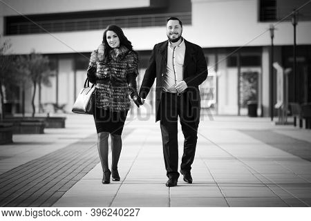 Happy young fashion couple walking on city street  Stylish trendy man in classic black coat and woman in fox fur jacket