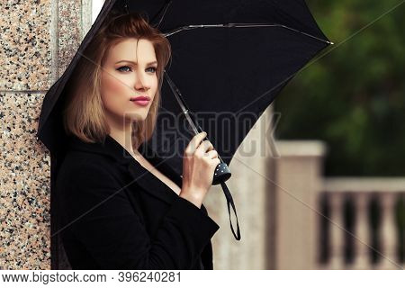 Young woman with umbrella leaning on the wall  Stylish fashion model in classic black coat