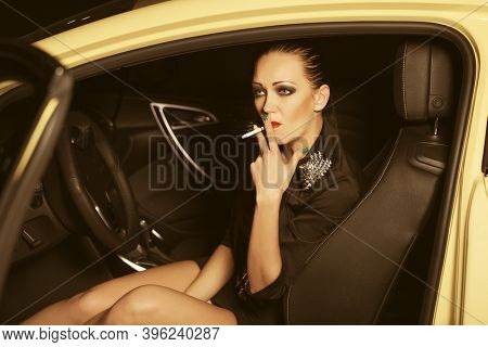 Young woman smoking cigarette in a car Stylish fashion model in black blazer and skirt
