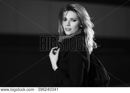 Young fashion blonde business woman walking on city street Stylish female model in classic black coat with leather handbag