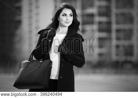 Happy young woman with leather tote handbag walking on city street Stylish fashion model in classic black coat and white pullover