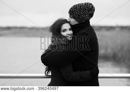 Happy young fashion couple in love Stylish man and woman in classic coats beanie and scarf