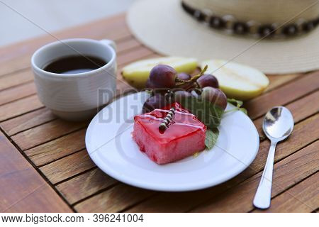 Still Life Of Food. White Plate With Red Cake And Grapes On A Wooden Table. Next To A Plate A Cup Of