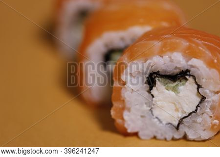 Food Background. Orange Rolls On An Orange Background. Rolls Philadelphia Close-up. Rolls With Salmo