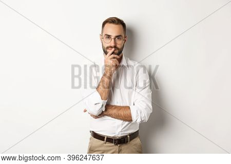 Thoughtful Handsome Businessman Looking At Camera, Making Choice Or Thinking, Standing In Glasses An