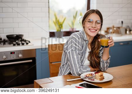 Smiling beautiful woman eating pancakes and drinking juice while having breakfast at home kitchen