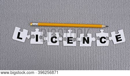Licence Is A Word Made Up Of Paper White Puzzles On A Gray Background And In Pencil. Info Concept