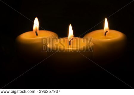 White Candles On A Dark Background. The Flame Of Three Candles Is Reflected In A Glass Ball On A Dar